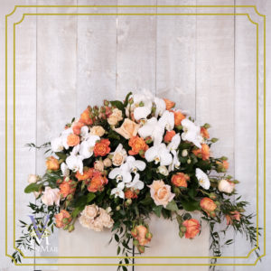 Casket Spray with hues of orange and white roses.